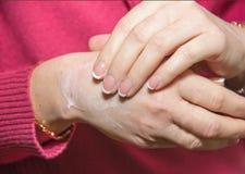 Aplicándose a las manos de la crema hidratante del cosmético, ablandando Foto de archivo
