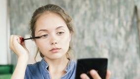 A aplicação à moda moderna da menina compõem e olhar no espelho video estoque