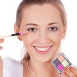A aplicação bonita da mulher compõe na cara fotografia de stock