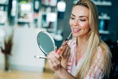 A aplicação bonita nova da mulher compõe usando o espelho pequeno Imagens de Stock Royalty Free