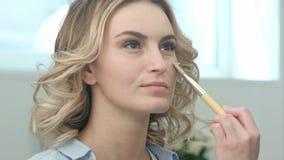 Aplicação da base para a cara modelo pelo artista profissional Fotografia de Stock Royalty Free