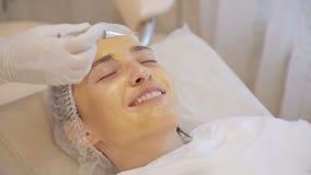 Aplicação de máscaras douradas na cara do modelo Fim acima video estoque