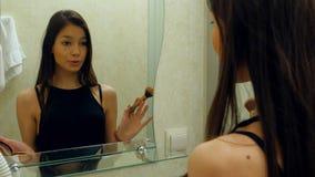 A aplicação do adolescente da beleza compõem e admirar-se no espelho imagem de stock