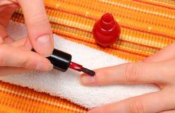 Aplicación de esmalte de uñas rojo, clavos manicured de la mujer Fotos de archivo libres de regalías