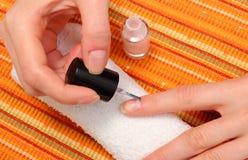Aplicación de esmalte de uñas rosado, clavos manicured de la mujer Fotos de archivo libres de regalías