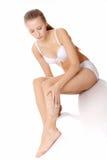 Aplicación de la crema de la crema hidratante en las piernas Imágenes de archivo libres de regalías