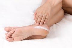 Aplicación de la crema a los pies Foto de archivo libre de regalías