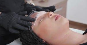 Aplicación de la hoja plástica en la crema que entumece para el retiro del tatuaje de la ceja metrajes
