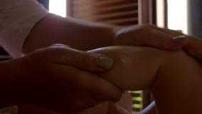 Aplicación de la mamá poner crema y masaje del bebé almacen de metraje de vídeo