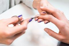 Aplicación de la manicura, cortando la cutícula con las tijeras imagen de archivo