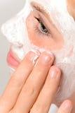 Aplicación de la piel de la belleza de la chica joven de los fingeres de la máscara Fotos de archivo