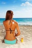 Aplicación de la protección del sol en piel bronceada Imagen de archivo libre de regalías