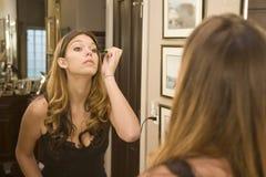 Aplicación de maquillaje en el espejo Imágenes de archivo libres de regalías