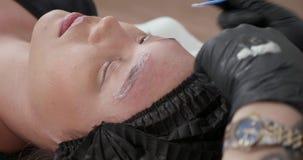 Aplicación del ácido glicólico en las cejas para sacar de la tinta la piel tatuada almacen de video