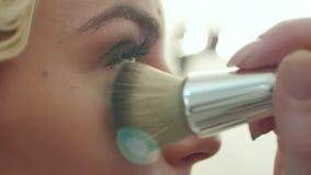 Aplicación del polvo cosmético con un cepillo grande en cara almacen de video