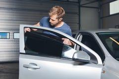 Aplicación teñiendo la hoja sobre una ventanilla del coche fotografía de archivo libre de regalías