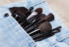 Aplicadores e escovas da composição no bolso das calças de brim Fotografia de Stock