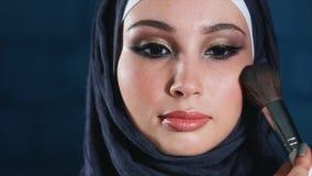 Aplicando a composição à mulher muçulmana bonita nova no lenço filme