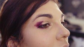 Aplicando lápiz de ojos púrpura en la esquina externa y el pliegue externo para crear ojos sin defectos de un smokey mire Caucási almacen de video
