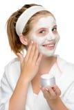 Aplicando a menina loura de sorriso dos dedos da máscara protetora Fotografia de Stock
