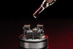 Aplicando o líquido com nicotina nas bobinas no RDA Fotografia de Stock Royalty Free