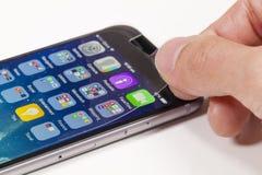 Aplicando o protetor da tela no telefone celular foto de stock