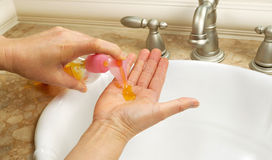 Aplicando o sabão líquido antes de lavar as mãos Imagem de Stock