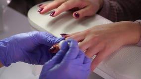 Aplicando o tratamento de mãos do óleo do prego filme