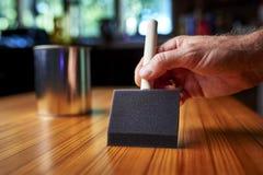 Aplicando o verniz a uma tabela de madeira Imagens de Stock