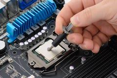 Aplicando a pasta térmica ao processador central Imagens de Stock
