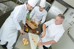 Aplikanci i doświadczony szef kuchni gotuje wpólnie zdjęcie stock