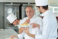 Aplikantów szefowie kuchni przy pracą z doświadczonym mistrzem zdjęcie stock