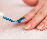 Aplique a obscuridade - verniz para as unhas azul no dedo indicador Fotos de Stock Royalty Free