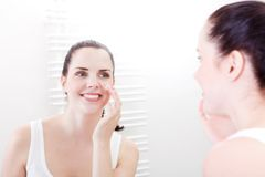 Apllying cream on face skincare stock image