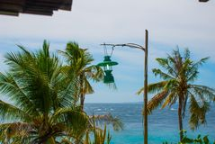 Apo海岛,菲律宾,在海岛海滩线的看法 棕榈树、海、灯笼和小船 库存图片