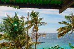 Apo海岛,菲律宾,在海岛海滩线的看法 棕榈树、海、灯笼和小船 免版税库存图片