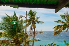 Apo-ö, Filippinerna, sikt på östrandlinje Palmträd, hav, lykta och fartyg Royaltyfri Bild