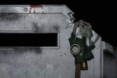 Apocalyps, gasmasker het hangen op een bunker op een zwarte achtergrond stock foto's