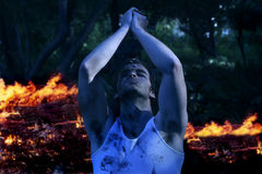 Apocalypse. Dramatic portrait of young emotional man with hands up praying in front of fire Royalty Free Stock Photography