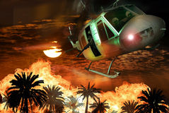 Apocalypse. An Augusta Bell helicopter, which served to Vietnam, flies over several palm trees in flames, under an orange fire rising sun Royalty Free Stock Photo