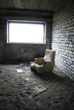 Apocalypse. Old dilapidated chair in an empty room with a window Stock Images