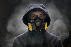 Apocalypse or armageddon concept. Man is wearing gas mask. A lot of smoke around. Stock Image