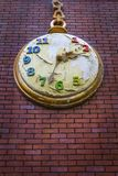 Apocalypse concept - Decorative pocket clock on a red bricks wall with peeled paint Stock Image