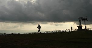 Apocalypse. Man walks lonely along the hill from the metal construction in the rays of evening lights and heavy grey sky stock footage