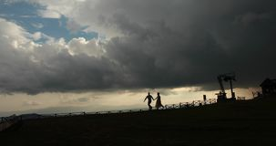 Apocalypse. Man and woman walk lonely along the hill from the metal construction in the rays of evening lights and heavy. Grey hangs over them stock footage