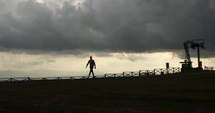 apocalypse Mann geht einsam entlang dem Hügel vom Metallbau in den Strahlen von Abendlichtern und von schwerem grauem Himmel stock footage
