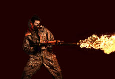 Apocalypse soldier with flamethrower. Dark background Royalty Free Stock Photos
