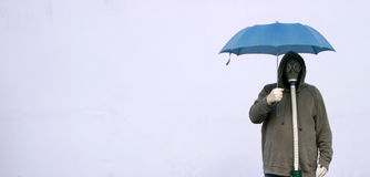 Apocalyptic acid rainy day. A man in a gas mask holds a blue umbrella to protect himself from the acid rain in a futuristic nuclear wastelandStrange, unique stock photo