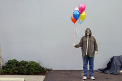 Apocalyptic birthday party. A man in a Gas Mask holds some colorful helium balloons in a futuristic nuclear wasteland for a birthday party of the few remaining royalty free stock images