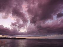 Apocalyptic sunset. Apocalyptic violet sunset with storm clouds over the strait of Messina Royalty Free Stock Image
